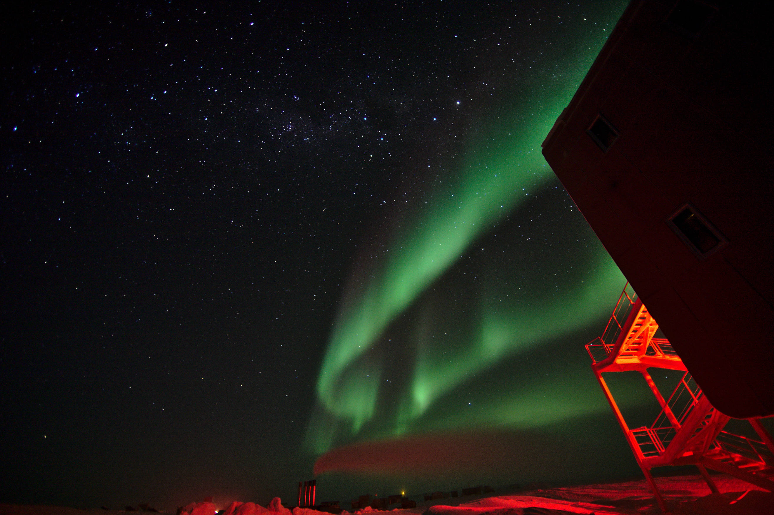 Auroras above the summer camp and power plant. To the right a corner of the station building with the red-illuminated emergency exits