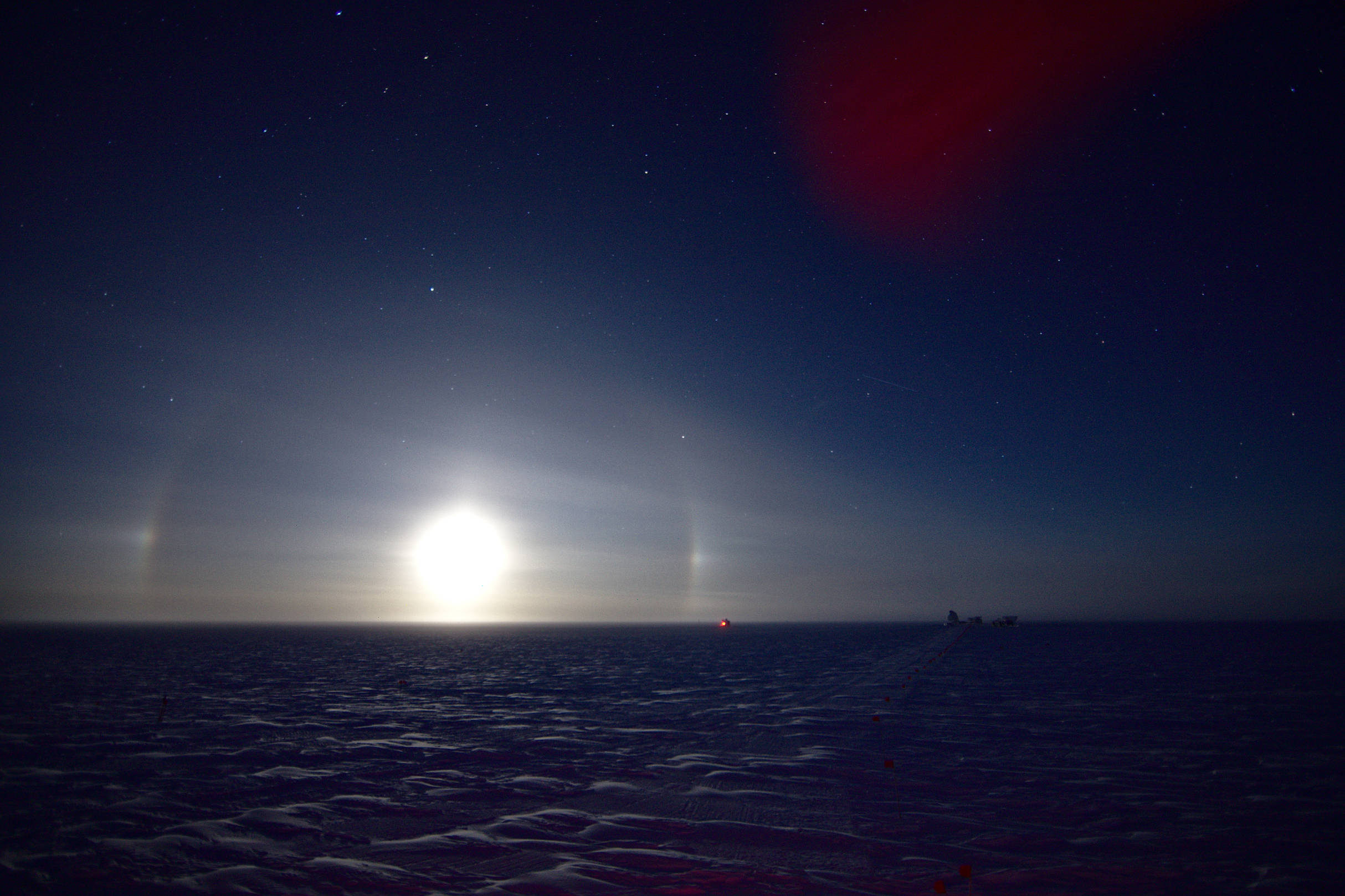 Ice crystals in the atmosphere cause the moonlight to form a partial halo and moon dogs around the full moon.