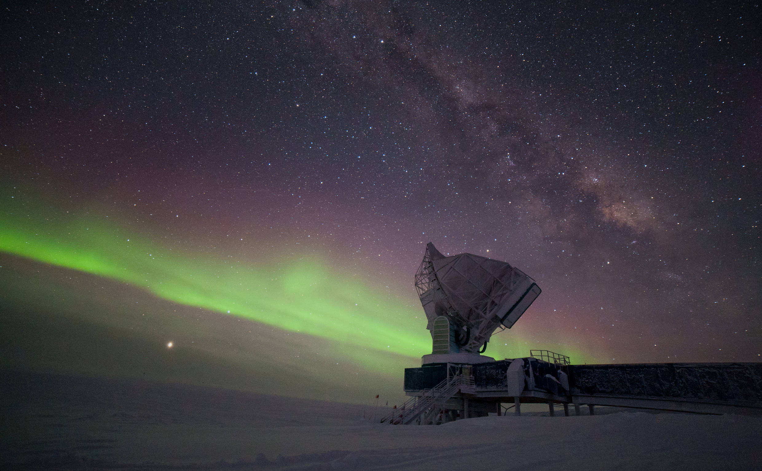 Taken in -60°C, this picture shows the South Pole Telescope illuminated by the Milky Way and some of the first aurora australis of the winter season 2017. Jupiter is brightly visible on the lower left, Saturn is to the right of the telescope dish.