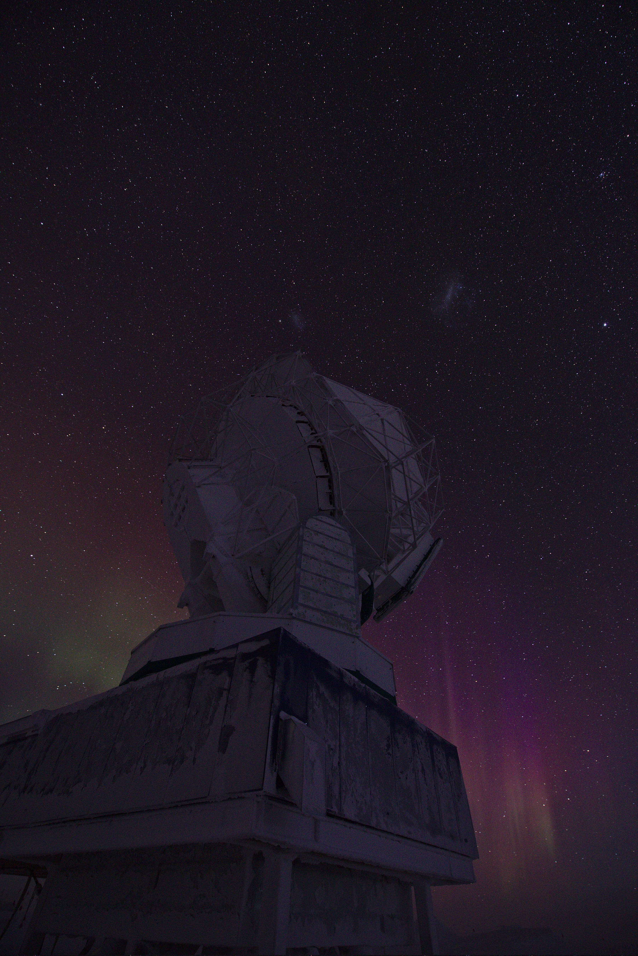 South Pole Telescope from below, with auroras on the horizon and the Magellanic Clouds above the telescope
