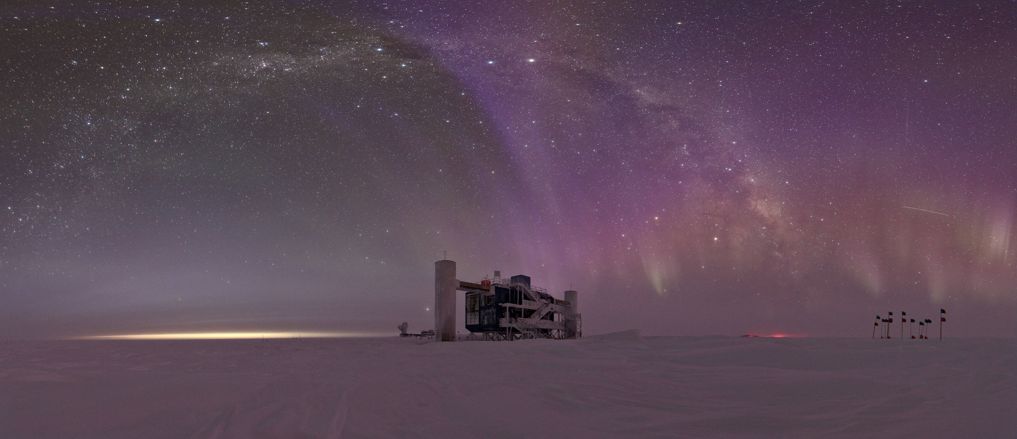 A wide angle shot of the auroras and the Milky Way above the IceCube Laboratory